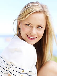 A woman smile to show how Inlays and Onlays can enhance your smile