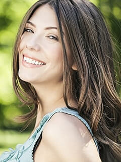A woman smiles to show how porcelain veneers can enhance your smile
