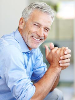 An older gentleman smiles to show how dental bridges restore your smile with a natural look and feel