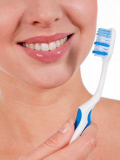 A woman holding a toothbrush shows the importance of dental hygiene
