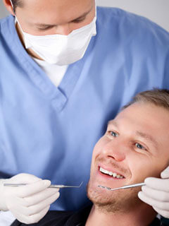 A dental hygienist working with a periodontal patient