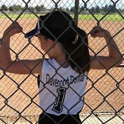 Little girl in softball uniform flexing